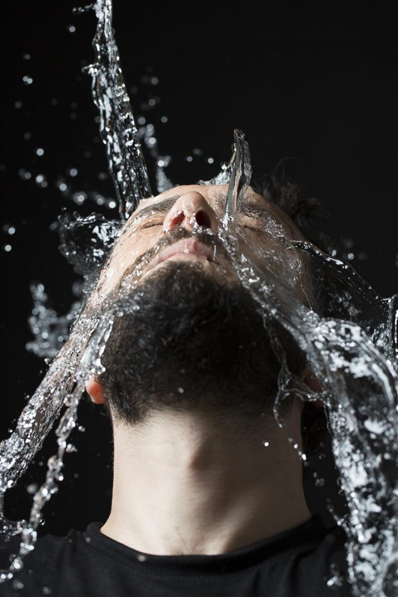portrait of man while water drops on his face like a waterfall