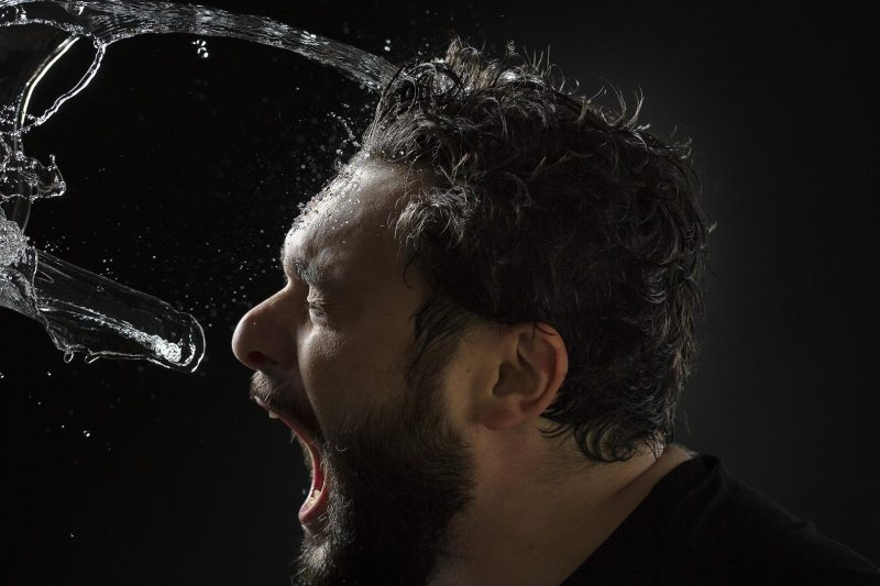 portrait of man while water drops on his face