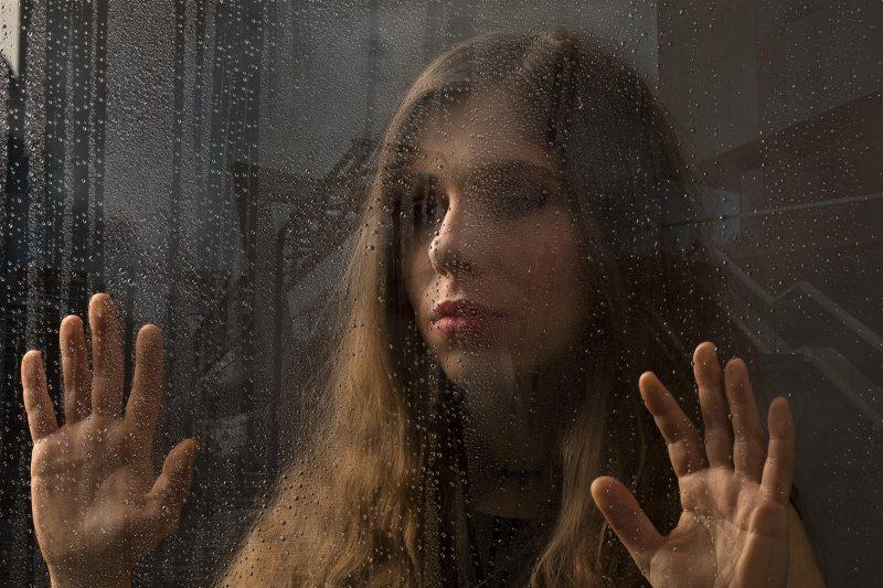 woman portrait through a glass during the rain