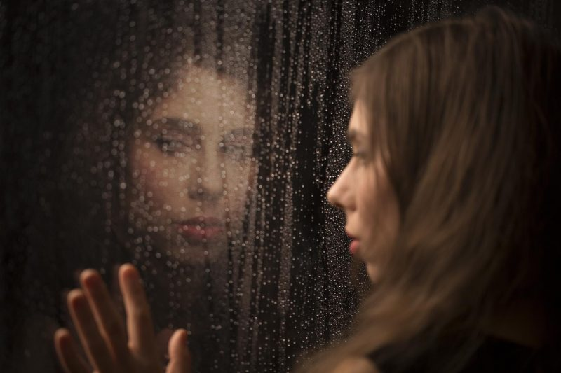 portrait of woman reflected from a window during the rain